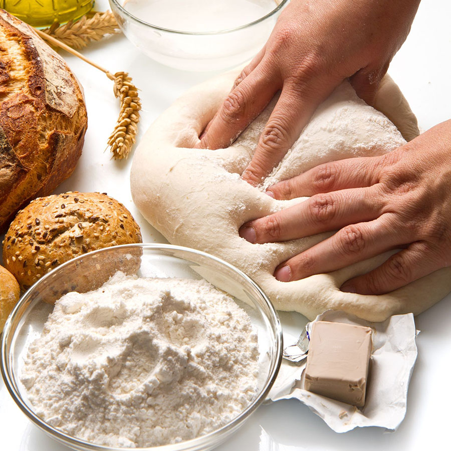 18669643 - female hands in flour closeup kneading dough on table